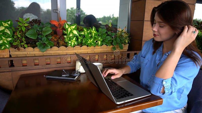 Freelancer die door smartphone spreken en met laptop bij koffie werken royalty-vrije stock afbeelding