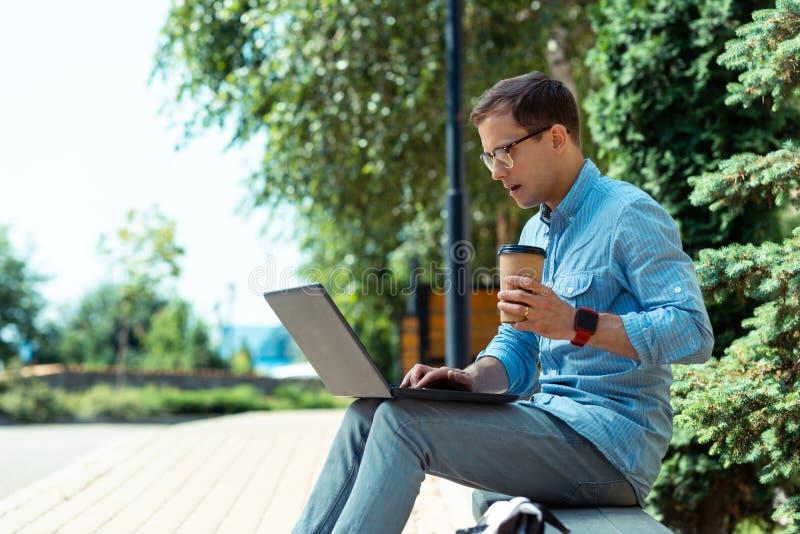 Freelancer die meeneemkoffie drinken en aan laptop buiten werken royalty-vrije stock foto's