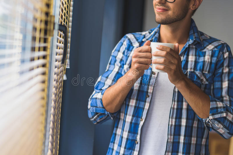 Freelancer die van thee voor een venster genieten stock foto's