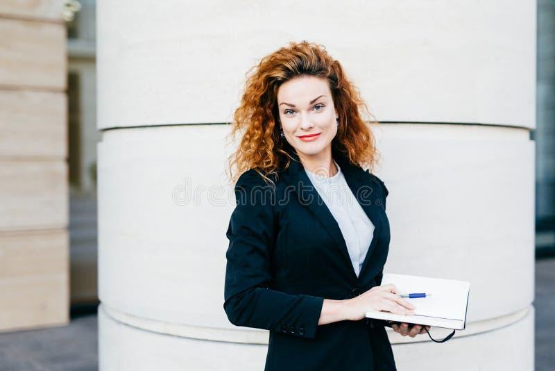 Freelancer fêmea com penteado espesso, a blusa branca vestindo, o revestimento preto e a saia, guardando seu livro do diário, esc fotografia de stock royalty free