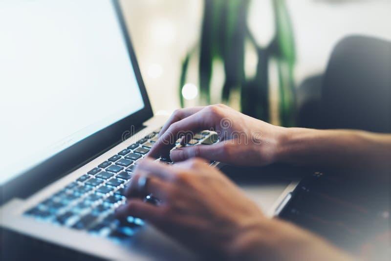 Freelancer fêmea do close up que senta o laptop aberto dianteiro com o monitor azul da tela vazia, trabalho novo da mulher de neg foto de stock
