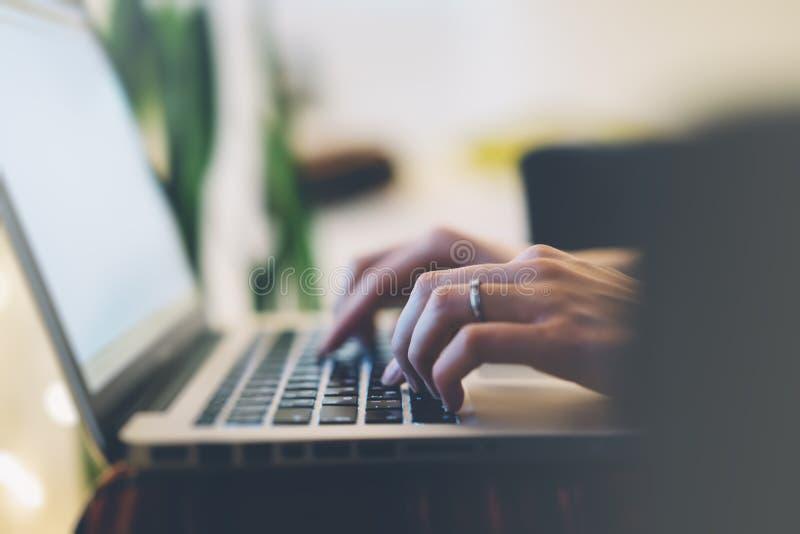 Freelancer fêmea do close up que senta o laptop aberto dianteiro com o monitor azul da tela vazia, trabalho novo da mulher de neg fotos de stock