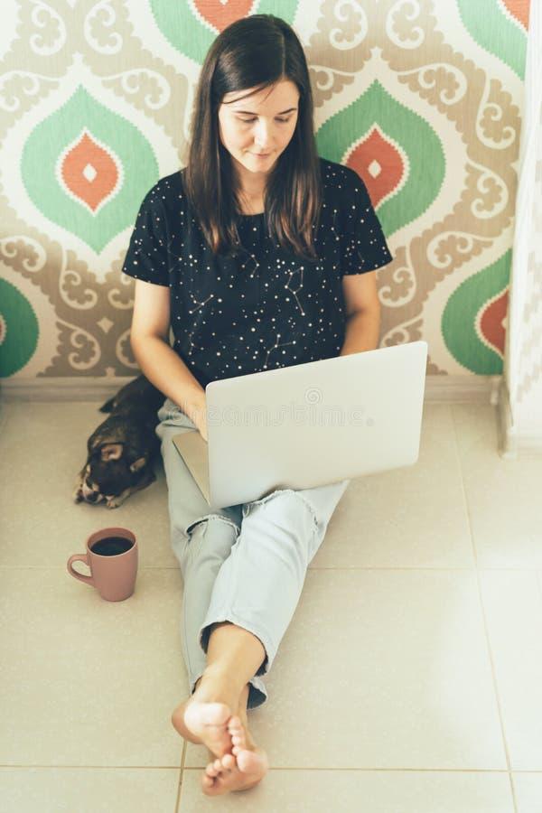 Freelancer fêmea em casa com um portátil fotografia de stock