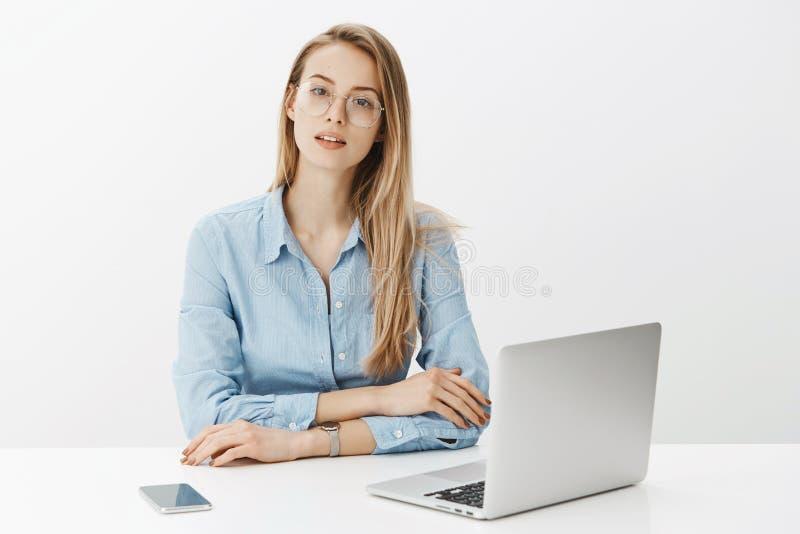 Freelancer fêmea esperto e talanted trabalhador que trabalha duramente no projeto novo que senta-se perto de vestir do portátil e fotos de stock