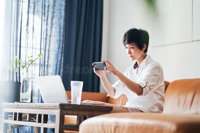 Freelancer f?mea asi?tico que senta-se no sof? que toma a foto com smartphone & que trabalha no port?til em casa imagens de stock