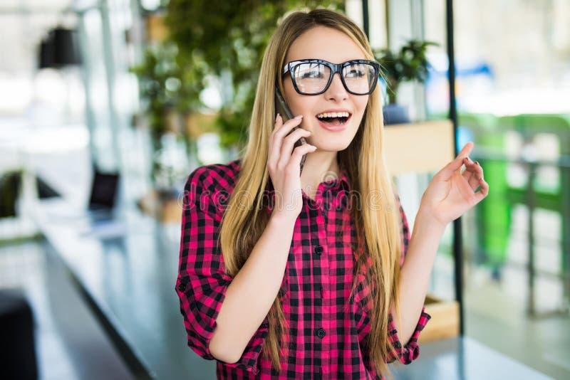 Freelancer gelukkige vrouw die op de mobiele telefoon met bureaugebouwen spreken op de achtergrond royalty-vrije stock afbeeldingen