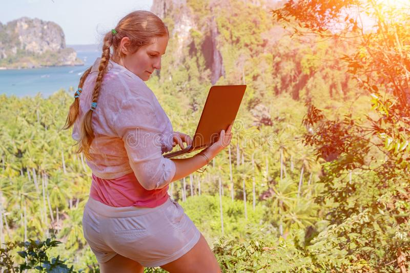 Freelancer girl with hair braids in white shirt working remotely from top of the mountain. She holds a laptop and typing email royalty free stock photos