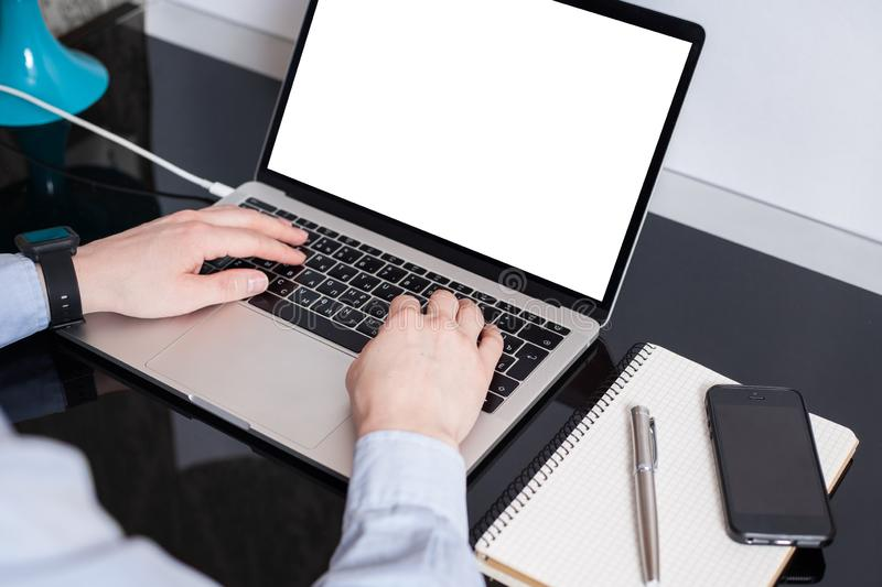 Freelancer at his working place. Empty laptop screen mockup. .A man is working by using a laptop mockup computer on vintage wooden. Table. Hands typing on a royalty free stock photography
