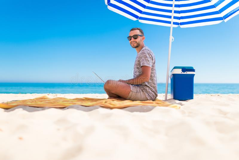 Freelancer, hombre de negocios acertado feliz en gafas de sol en la vocación con el ordenador portátil en la playa debajo del par imágenes de archivo libres de regalías