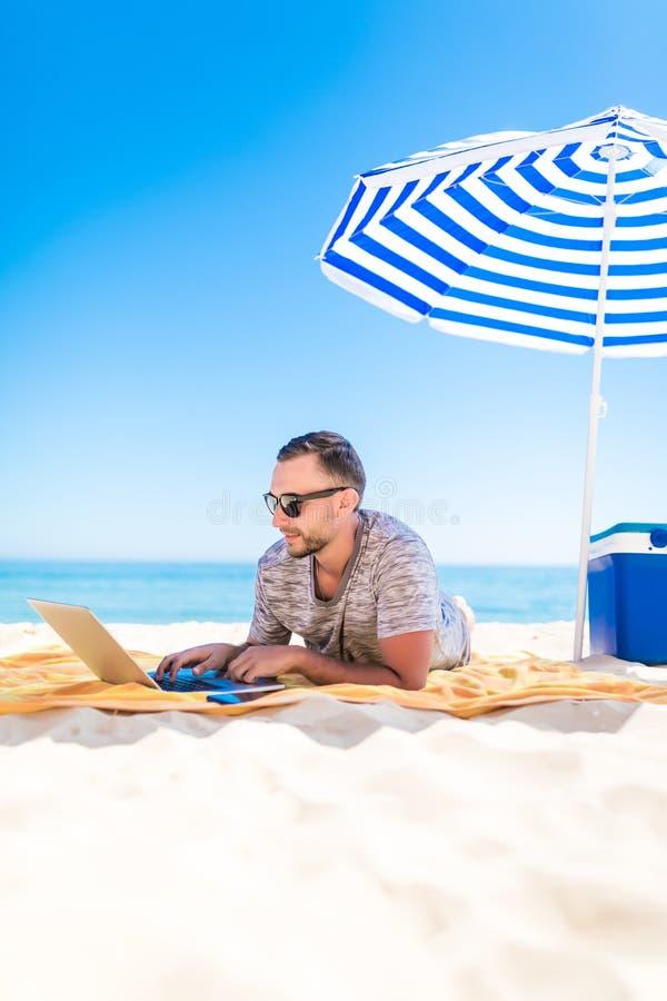 Freelancer, hombre de negocios acertado feliz en gafas de sol en la vocación con el ordenador portátil en la playa debajo del par fotos de archivo libres de regalías