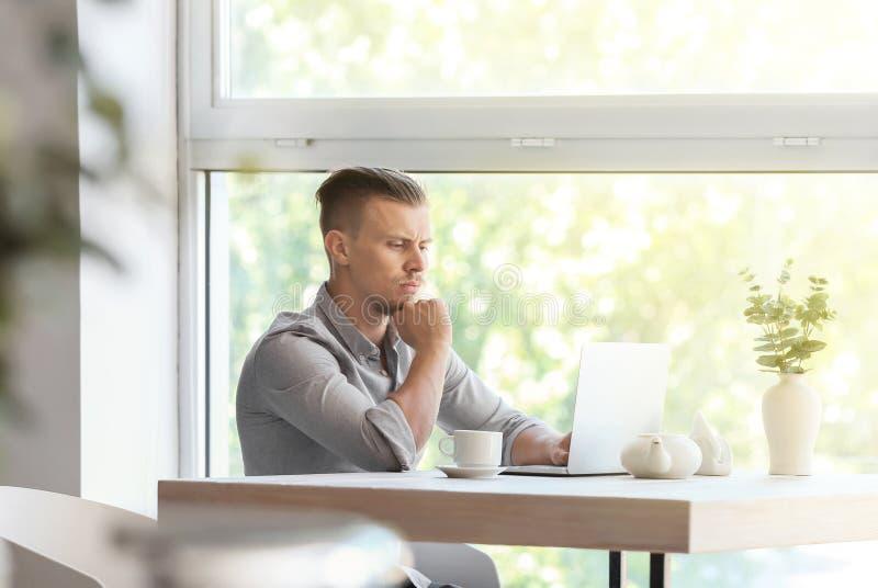 Freelancer incomodado que trabalha no portátil no café imagens de stock