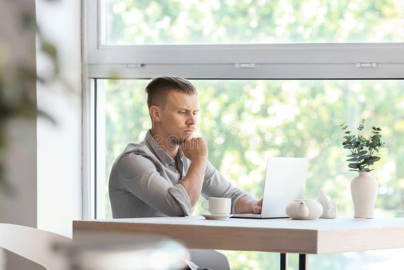 Freelancer incomodado que trabalha no portátil no café fotografia de stock