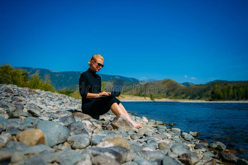 Freelancer with laptop on the nature. Blogger hipster traveler business lady pretty girl  works outdoor. Young blondy woman in stock photography