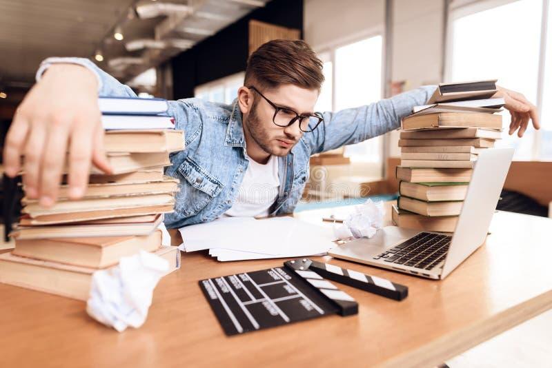 Freelancer mężczyzna patrzeje notatki udaremniać przy laptopu obsiadaniem przy biurkiem otaczającym książkami obrazy stock