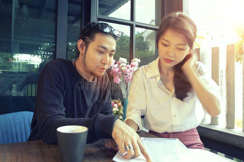 Freelancer mais novo asiático que fala sobre o documento de trabalho na casa fora fotografia de stock royalty free