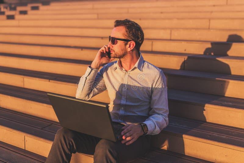 Freelancer moderno que invita a smartphone, sosteniendo el ordenador portátil y sentándose en pasos afuera en la puesta del sol imagen de archivo