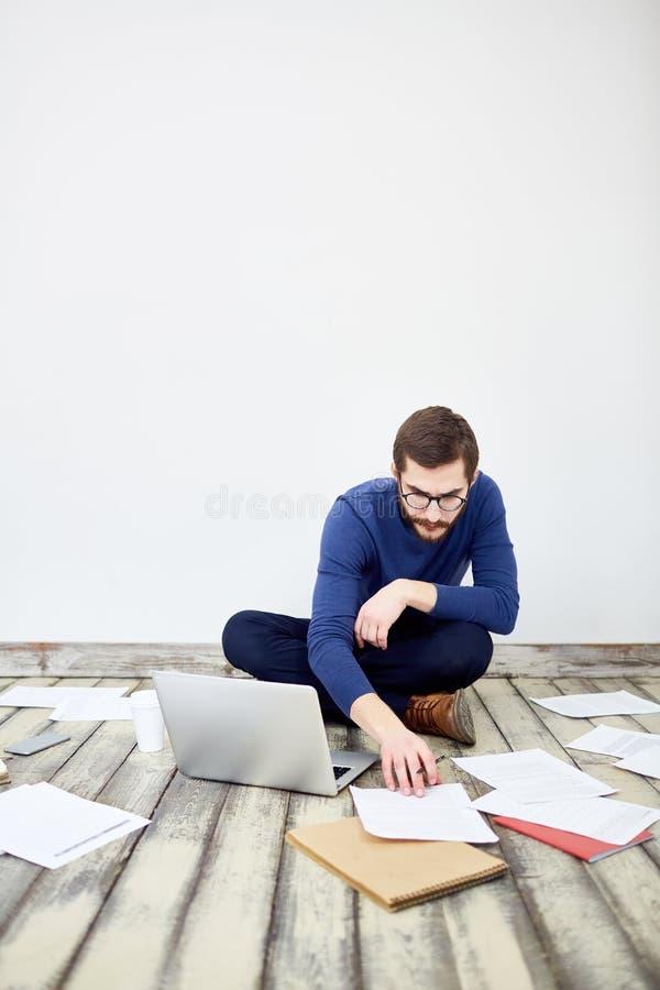 Freelancer moderno que trabaja en piso imagen de archivo libre de regalías