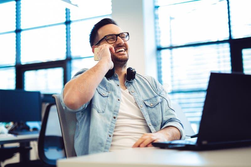 Freelancer opowiada na telefonie podczas gdy używać laptop przy biurem zdjęcia royalty free