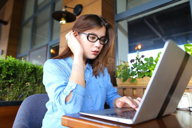 Freelancer opowiada smartphone i działaniem z laptopem przy kawiarnią zdjęcia stock