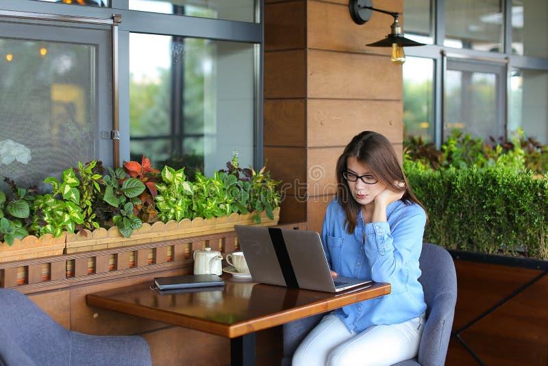 Freelancer opowiada smartphone i działaniem z laptopem przy kawiarnią obrazy royalty free