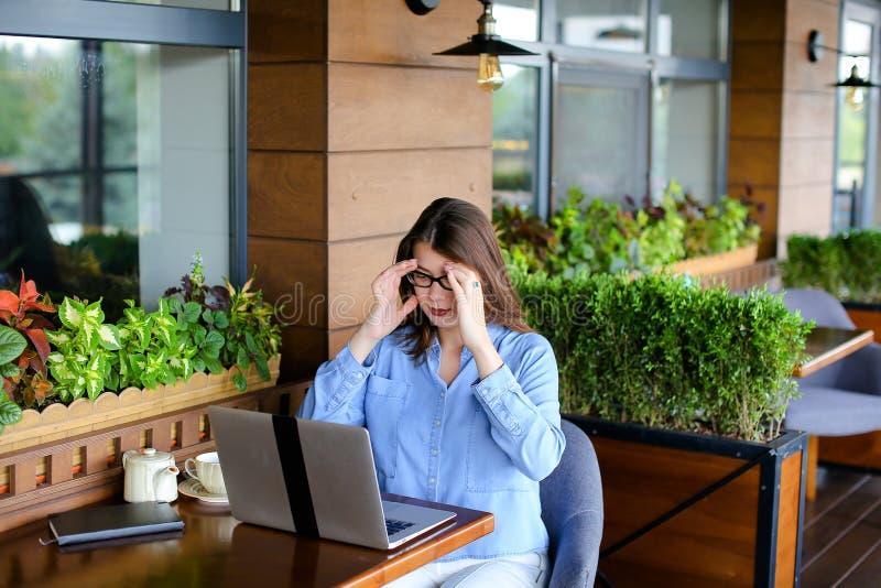 Freelancer opowiada smartphone i działaniem z laptopem przy kawiarnią zdjęcie royalty free