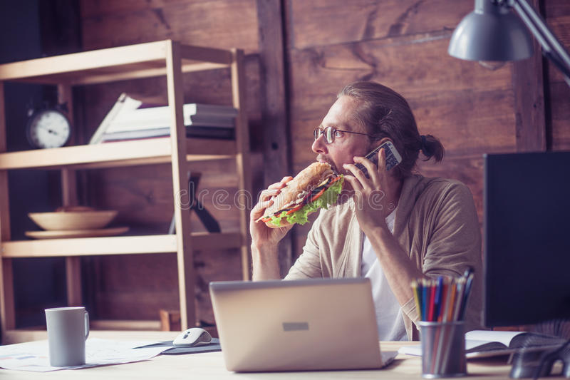 Freelancer que come o sanduíche ao falar no telefone foto de stock