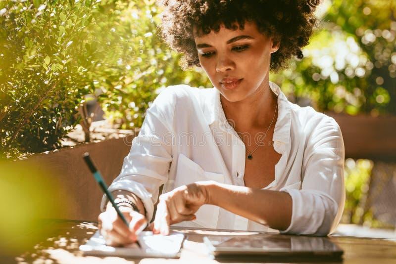 Freelancer que trabaja en el café al aire libre imagen de archivo libre de regalías