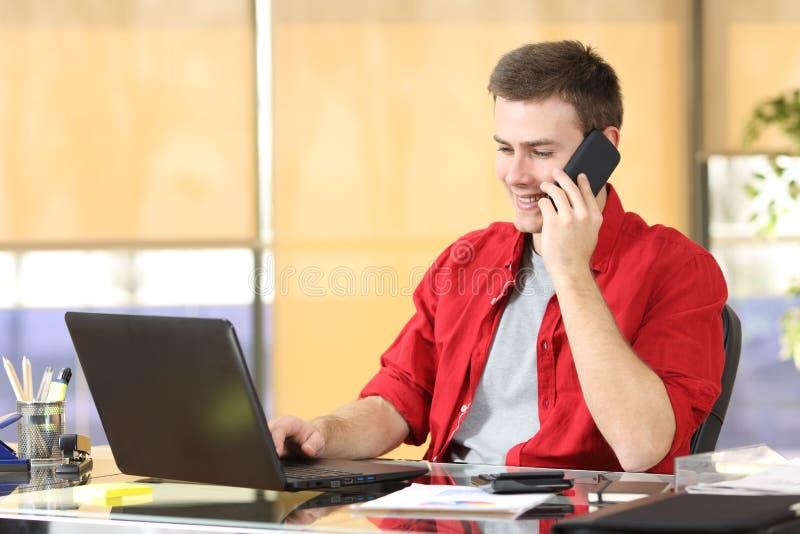 Freelancer que trabalha na linha e que chama pelo telefone fotografia de stock