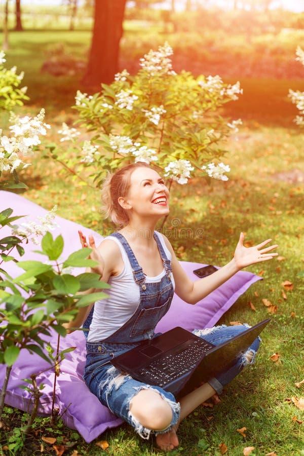 Freelancer que trabalha no jardim Escrita, surfando no Internet Jovem mulher que relaxa e que tem o divertimento na área do parqu fotos de stock royalty free