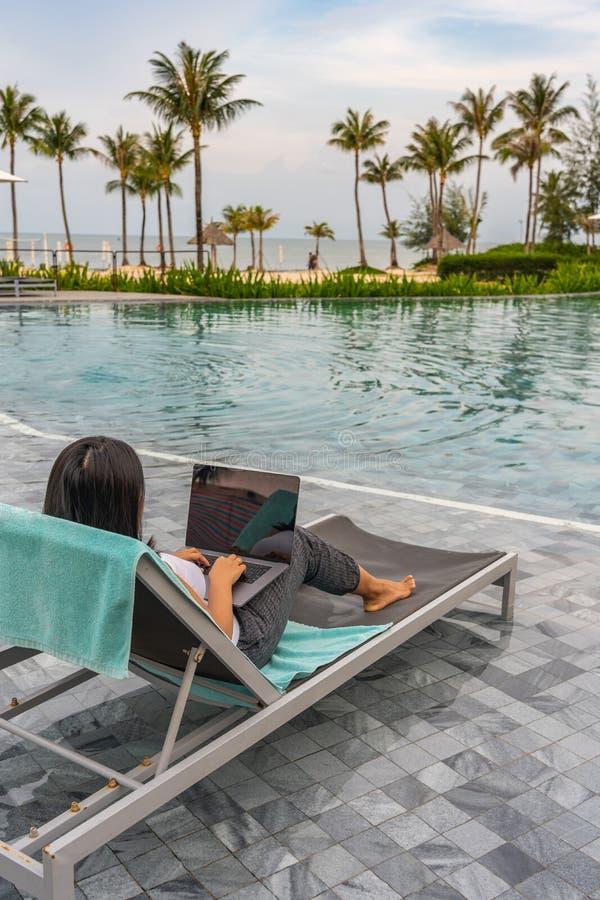 Freelancer que usa o portátil pela piscina bonita na praia imagem de stock royalty free