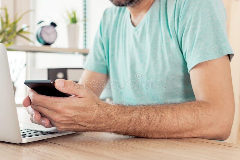 Freelancer som använder den smarta telefonen i inrikesdepartementet arkivbilder