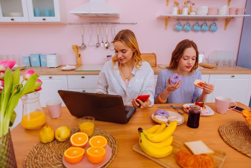 Freelancer som arbetar i morgonen som sitter nära tonårs- sibling royaltyfria foton