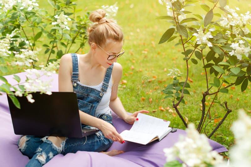 Freelancer som arbetar i trädgården Skriva och att surfa i internet Den unga kvinnan som kopplar av och har gyckel parkerar in, o arkivfoton