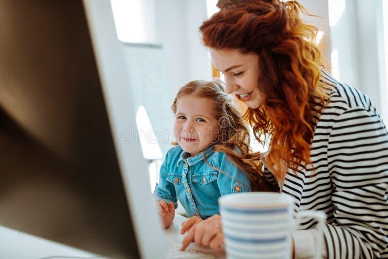 Freelancer som ler stund som arbetar nära hennes älskvärda dotter arkivfoton