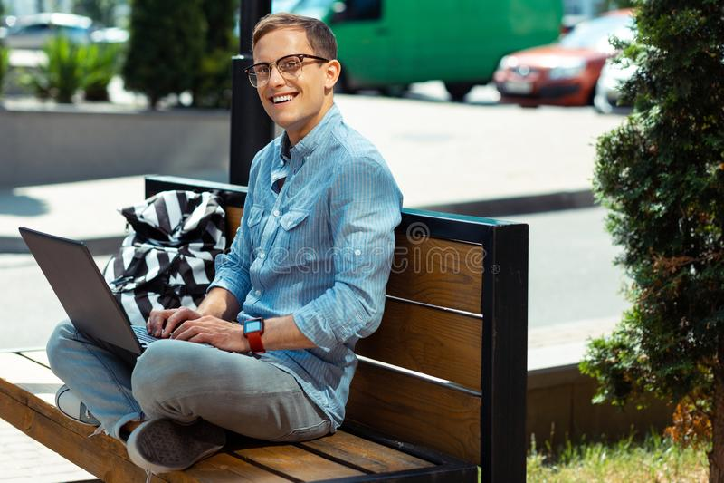 Freelancer som tycker om arbete på bärbara datorn, medan sitta i bostadsområde royaltyfria bilder
