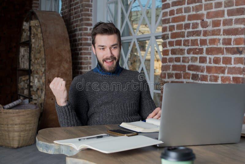 Freelancer sonriente del hombre que aumenta la mano en el gesto del sí, victoria de la celebración, mirando en el ordenador portá fotos de archivo