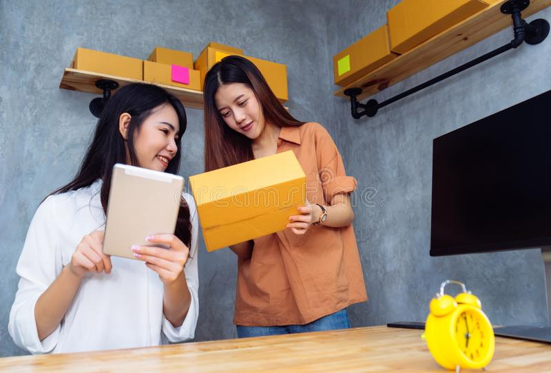 Freelancer teenager asian women teamwork sme business. Working at office in home interior writing address,checking order for customer and online delivery for stock photos
