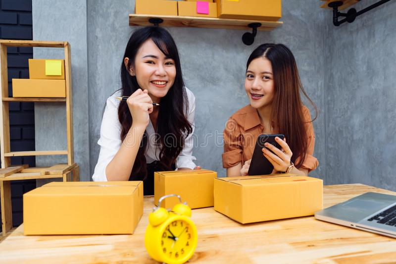 Freelancer teenager asian women teamwork sme business. Working at office in home interior writing address,checking order for customer and online delivery for royalty free stock photography