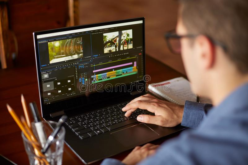 Freelancer video editor works at the laptop computer with movie editing sofware. Videographer vlogger or blogger camera stock photo