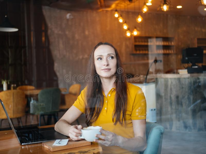 Freelancer woman enjoying cofee or cocoa while working in cafe royalty free stock image