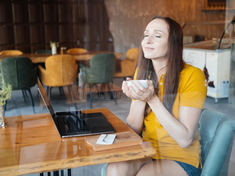 Freelancer woman enjoying cofee or cocoa while working in cafe royalty free stock images
