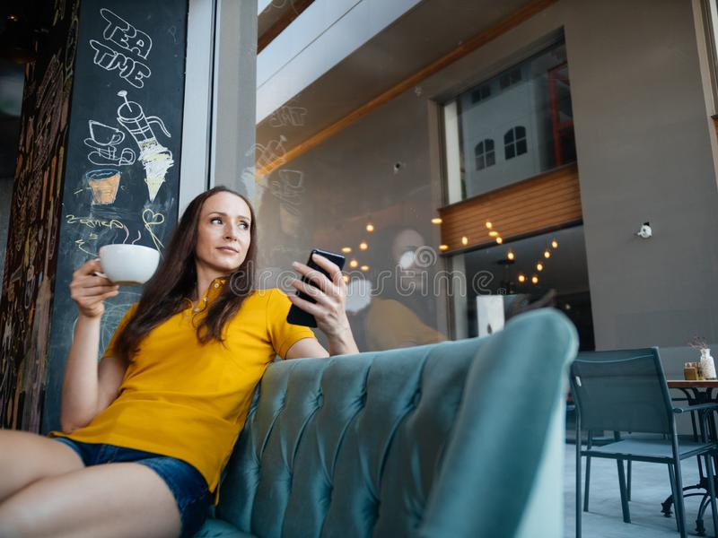Freelancer woman using smartphone laptop in cafe texting sharing on social media royalty free stock photo