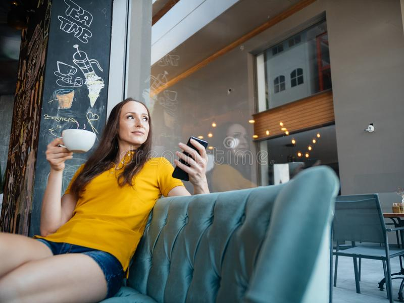 Freelancer woman using smartphone laptop in cafe texting sharing on social media stock images