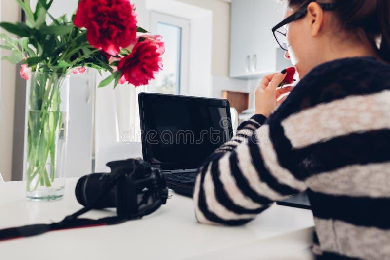 Freelancerfotograf som arbetar i morgonkök Kvinnan arbetar på bärbara datorn genom att använda kamera- och pennminnestavlan royaltyfria foton