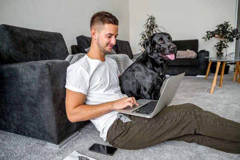 Freelancergrabb som sitter hemmastatt arbete i bärbar dator och med hunden in arkivfoto
