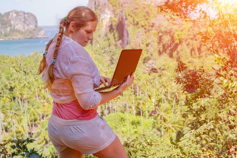 Freelancermeisje met haarvlechten in wit overhemd die ver vanaf bovenkant van de berg werken Zij houdt laptop en het typen e-mail royalty-vrije stock foto's
