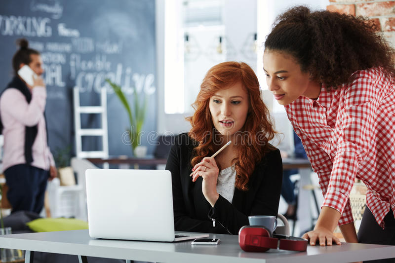 Freelancers in coworking office. Young freelancers using the laptop in modern coworking office royalty free stock images