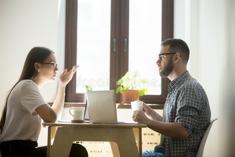 Freelancers en cuestión que negocian y que trabajan en los ordenadores portátiles imagen de archivo