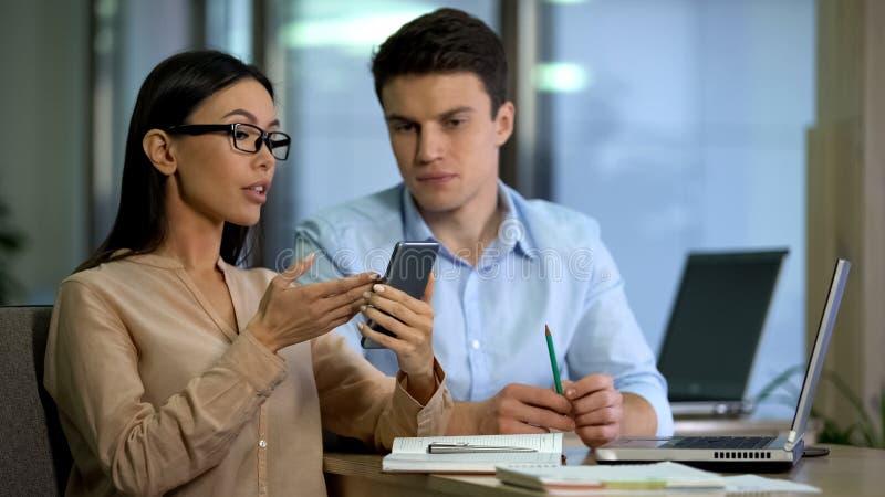 Freelancers novos que testam a aplica??o do smartphone, tecnologia moderna, dispositivo imagens de stock