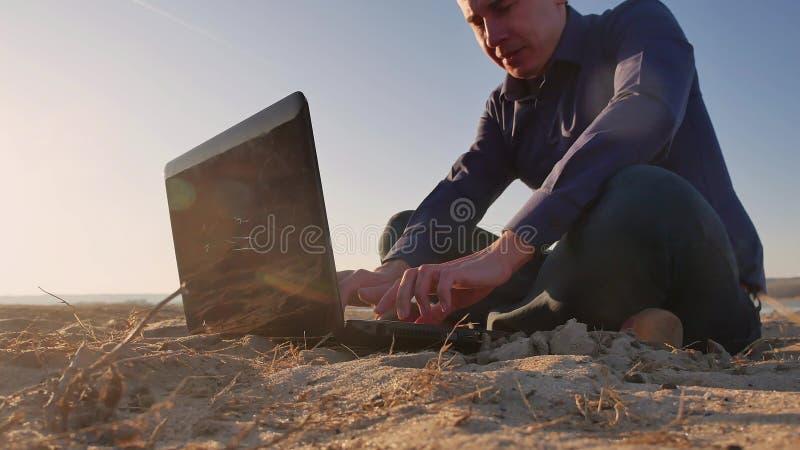 freelancing Sirva el trabajo en el ordenador portátil en la naturaleza, freelancer que trabaja independientemente, trabajo del ho fotos de archivo